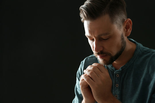 Man with hands clasped together for prayer on black background. Space for text