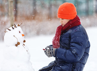 Pretty boy in warm blue jacket, red hat makes a snowman at winter day. Winter activities, fun