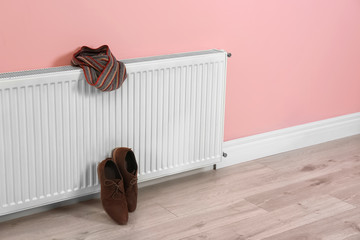 Heating radiator with scarf and shoes near color wall, Space for text