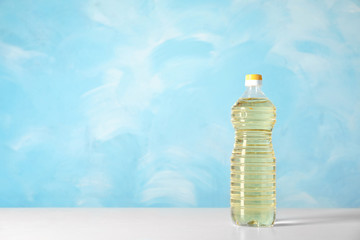 Bottle of oil on table against color background. Space for text