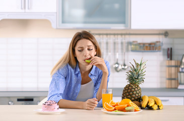 Woman choosing between dessert and fruits at table in kitchen. Healthy diet