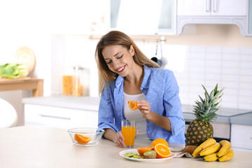 Woman making orange juice at table in kitchen. Healthy diet
