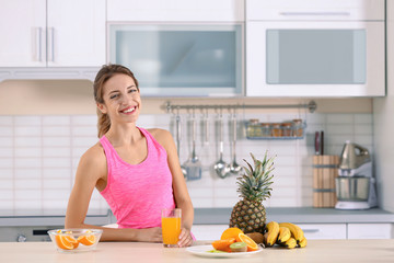 Woman with glass of orange juice on table in kitchen. Healthy diet