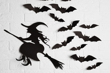 Paper bats and witch cutout on brick wall. Halloween decor