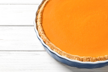 Fresh delicious homemade pumpkin pie and space for text on wooden background