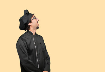 young crazy man as a chef smiling and looking up and sideways, towards the sky or to the spot where the publicist may place a concept or message.