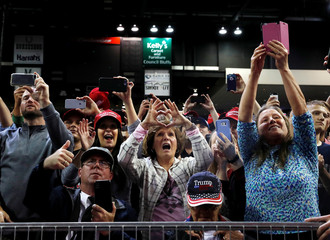 People cheer during a campaign rally by U.S. President Donald Trump in Council Bluffs