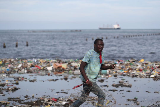 A man runs in front of plastic and other debris  on the shores of Cap Haitian beach, in Cap Haitian