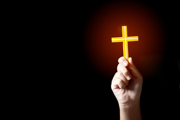 Human hand holding and lift of christian cross with light black background