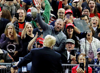 People cheer as U.S. President Donald Trump holds a campaign rally in Council Bluffs