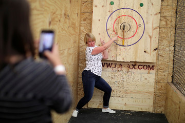 Leslie Parker poses for a friend's photo after hitting a bull's eye in axe throwing, a sport that started in the Canadian backwoods and is growing in popularity in U.S. cities, at LA Ax in North Hollywood, Los Angeles