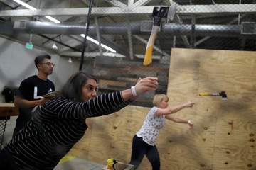 Faith Aids participates in axe throwing, a sport that started in the Canadian backwoods and is growing in popularity in U.S. cities, at LA Ax in North Hollywood, Los Angeles