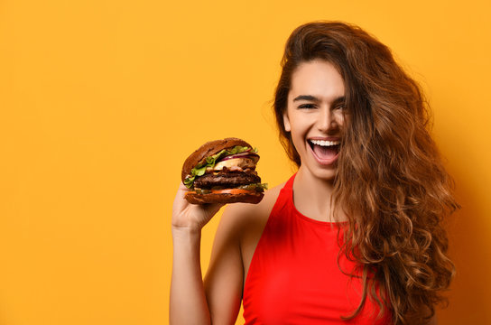 Woman hold big barbecue burger sandwich with hungry mouth happy screaming laughing on yellow background