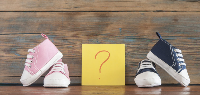 baby shoes and paper sticker with question mark on wooden background. Concept of choosing baby name
