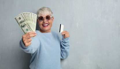 senior cool woman with a credit card against grunge cement wall. money or savings concept.