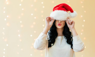 Woman with a Santa hat pulled over her eyes on a shiny light background