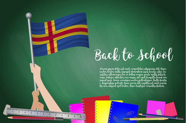 Vector flag of Aland on Black chalkboard background. Education Background with Hands Holding Up of Aland flag. Back to school with pencils, books,