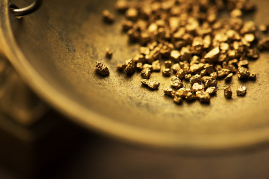 Trade and exchange. Weighing a gold nugget on a old brass scale dish.for trading. Shallow depth of field.