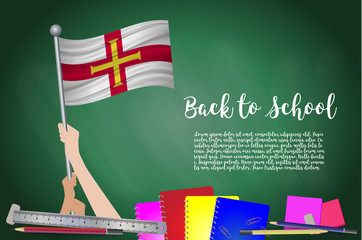 Vector flag of guernsey on Black chalkboard background. Education Background with Hands Holding Up of guernsey flag. Back to school with pencils, books