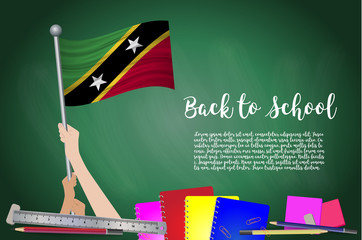 Vector flag of Saint Kitts and Nevis on Black chalkboard background. Education Background with Hands Holding Up of Saint Kitts and Nevis flag. Back to school with pencils, books