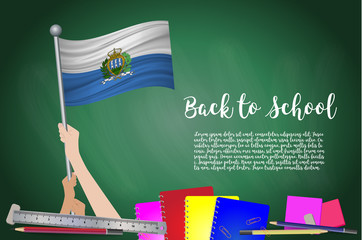 Vector flag of San Marino on Black chalkboard background. Education Background with Hands Holding Up of San Marino flag. Back to school with pencils