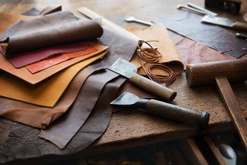 Leather craft or leather working. Selected pieces of beautifully colored or tanned leather on leather craftman's work desk . Piece of hide and working tools on a work table. Wall mural