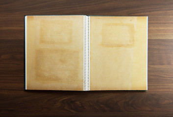 Blank page of an 1970s photo album, on a dark colored wooden table. Wall mural