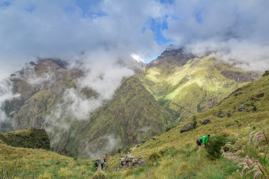 Blue cloudy sky above verdant green mountains and hikers on the Inca Trail in Peru
