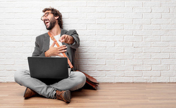 young man sitting on the floor laughing hard at something hilarious and pointing towards you while holding belly with the other hand, having a good time with funny jokes.