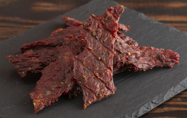 Pile of Black Pepper Beef Jerky on a Rustic Wooden Table