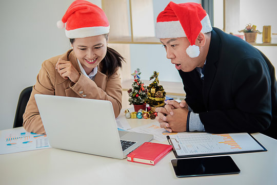 Group of young business people are sitting in Santa hats in last working day. young creative people are celebrating holiday in modern office. Merry Christmas and Happy New Year 2018