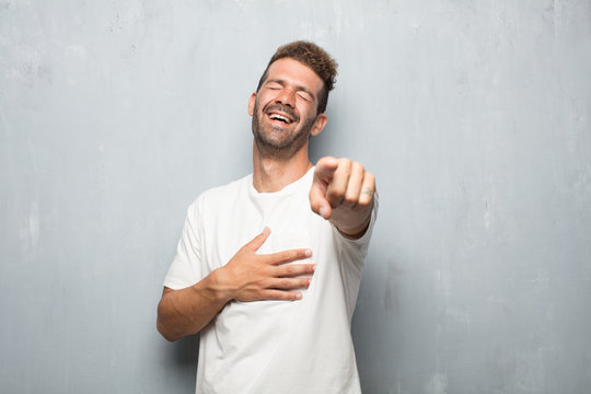 young handsome man laughing hard at something hilarious and pointing towards you while holding belly with the other hand, having a good time with funny jokes.