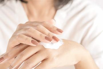 beautiful woman hand with nail polish applying hand cream