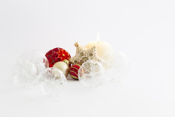 Still life with beautiful decorative transparent and red christmas glass balls, a round satin colored burning candle and a satin star ornament on white background