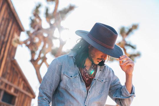 Cowboy with blue shirt and long black hair