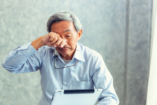 Senior Asian Man Has Eyes Problems With His Vision While Trying to Read Message in Tablet. Close-Up of Elderly Old Male Having Long/Far Sighted and Eye Fatigue When He Looking Screen Tablet Long Time