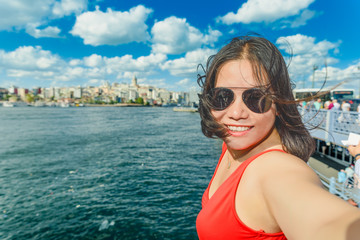 Beautiful woman takes selfie with view of Galata Tower