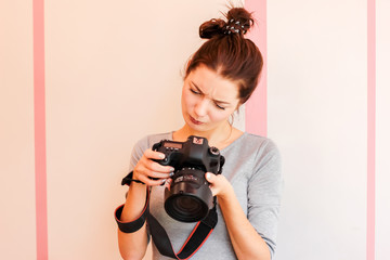 Pretty girl photographer looks into her camera and makes funny face