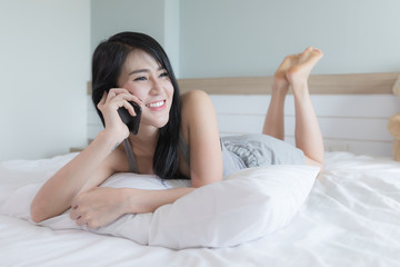 woman Asian girl talking with friend on smartphone in bedroom on weekend