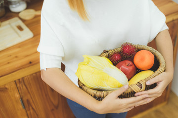 Asian beautiful woman holding fruit and vegetable in the kitchen at her home. Happy pretty asian female eat freshness fruit for healthy body. lifestyle asia woman at home concept.