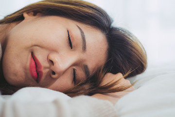 Beautiful young Asian woman sleeping in bed in the morning. Attractive asian girl use bedtime in her comfortable bedroom. Relaxation bedroom. Iifestyle asia woman at home concept.