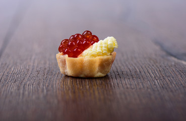 Tartlet with red caviar and butter on a wooden background