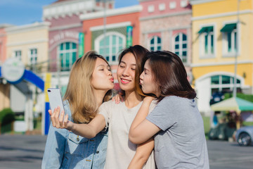 Attractive beautiful asian friends women using a smartphone. Happy young asian teenage at urban city while taking self portraits with her friends together with a smartphone.