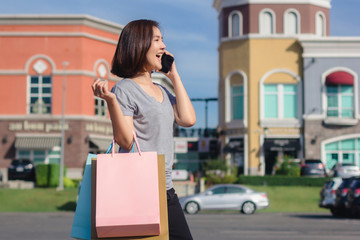 Beautiful young shopaholic Asian woman using smartphone for talking while she walking to buy cosmetics, clothes etc. with shopping bags in their hands. Lifestyle woman enjoy her holidays concept.