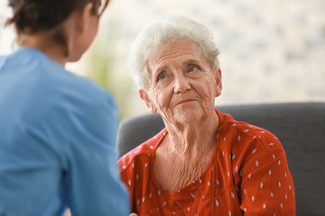 Young nurse visiting elderly woman at home