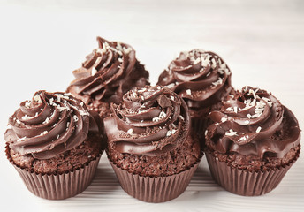 Tasty chocolate cupcakes on white wooden table