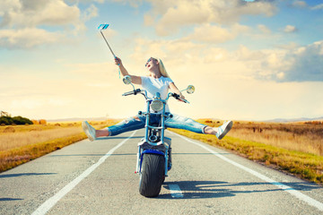 Girl biker riding a motorbike on an asphalt road and photographed.