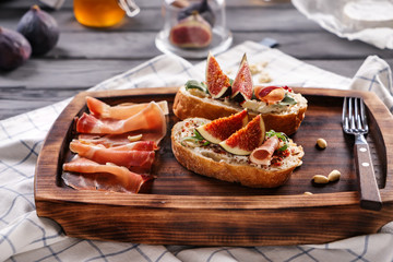 Tasty sandwiches with ripe fig and prosciutto on wooden board