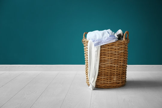 Laundry basket with dirty clothes on floor near color wall