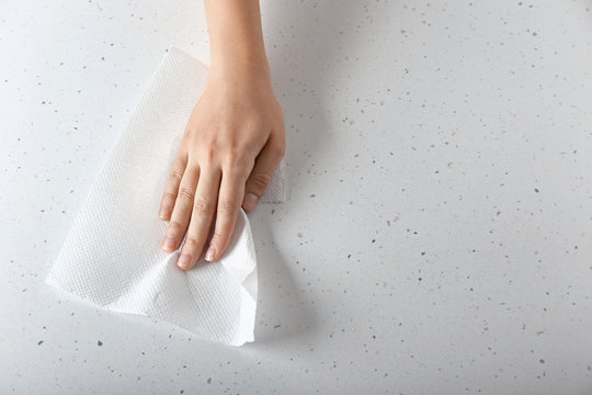 Woman wiping light table with paper towel